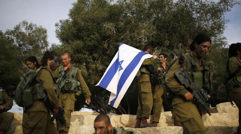 "An Israeli soldier of the Caracal battalion holds an Israeli flag after finishing a 20-kilometre march in Israel's Negev desert, near Kibbutz Sde Boker, marking the end of their training, May 29, 2014. The ""Caracal"" battalion, two-thirds of whose members are women, was established in 2004 with the purpose of incorporating female soldiers in combat units. The main mission of Caracal is routine patrols on Israel's border with Egypt to intercept infiltrators and smuggling from the Sinai desert. REUTERS/Amir Cohen (ISRAEL - Tags: MILITARY)"