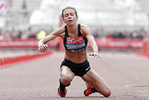 Great Britain's Hayley Carruthers collapses before the finish line in the women's race at the 39th London Marathon in London, Sunday, April 28, 2019. (AP Photo/Alastair Grant)
